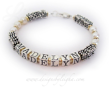 DBL-PS4-Gold - 1 String  Enter: MADELYN  This is a 1-string with 1 name 14k gold-filled, .925 sterling silver square Bali and Swarovski Pearl Name Bracelet. It is shown with Madelyn and they upgraded to a Heart Lobster claw clasp.