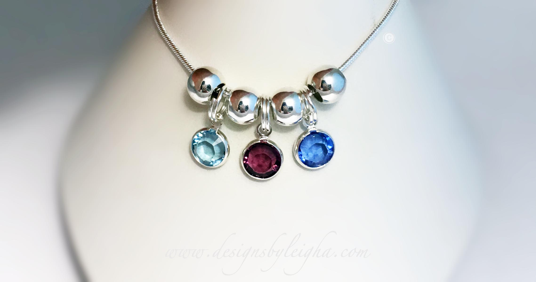 This Swarovski Crystal Birthstone Charm necklace is shown with 3 birthstones: March or Aquamarine, February or Amethyst, and September or Sapphire.