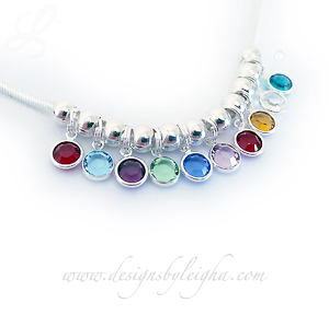 This Birthstone Charm Necklace is shown with 10 Swarovski Birthstone Charms: January or Siam, March or Aquamarine, February or Amethyst, August or Peridot, September or Sapphire, June or Light Amethyst, July or Siam, November or Topaz April or Diamond and December or Blue Zircon Birthstone Charms by Swarovski.