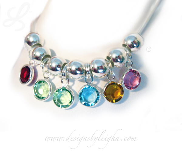 This Birthstone Charm Bracelet is shown with 6 Swarovski Birthstone Charms: January or Siam, 2- August or Peridot, March or Aquamarine, November or Topaz and October or Rose Birthstone Charms by Swarovski.
