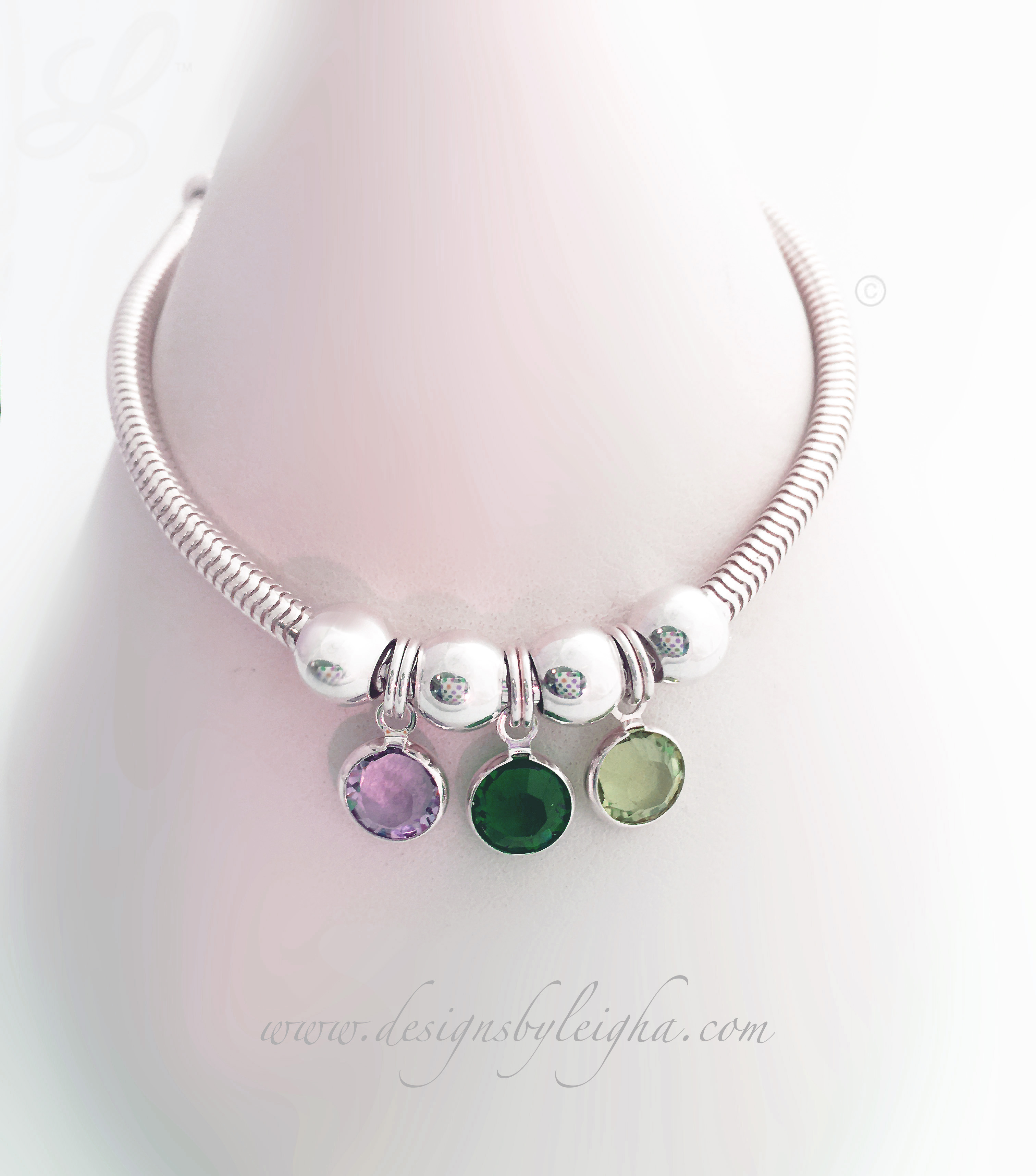 This Birthstone Charm Bracelet is shown with 3 Swarovski Birthstone Charms: June or Light Amethyst, May or Emerald and August or Peridot.