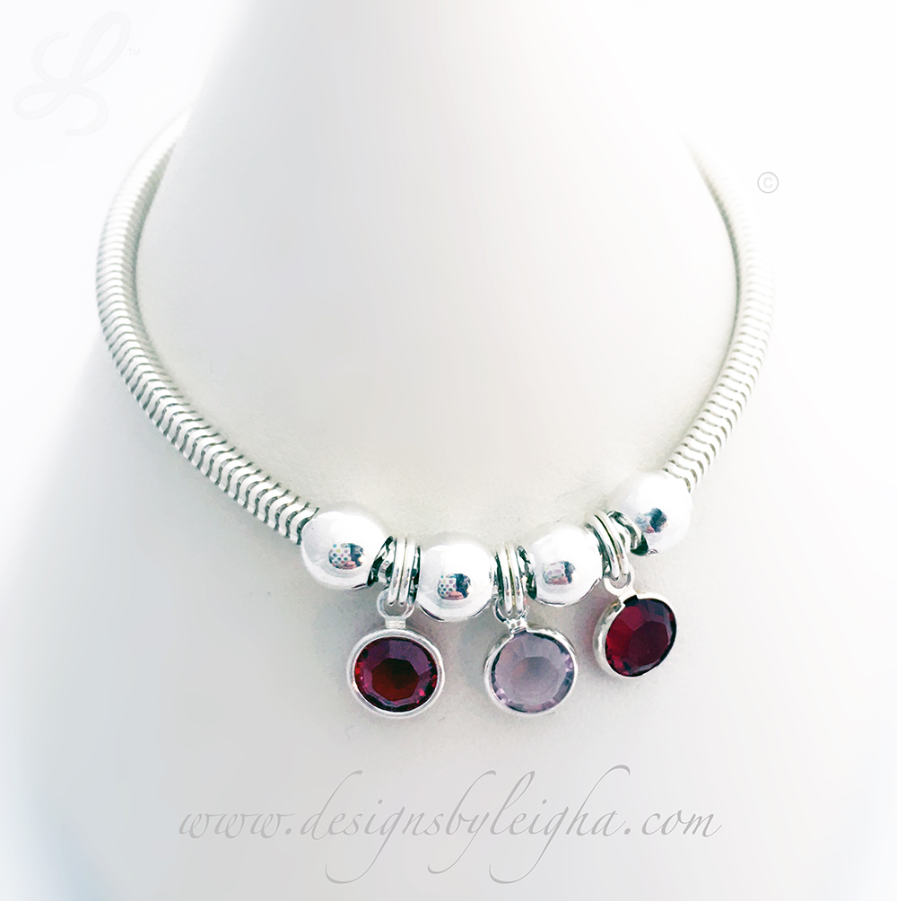 This Birthstone Charm Bracelet is shown with 3 Swarovski Birthstone Charms: January or Siam, June or Light Amethyst and July or Siam Birthstone Charms by Swarovski.