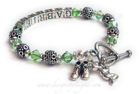 This Bali Birthstone Bracelet is shown with 1-string and 1 name. They put Gabriel and choose the Peridot or August Birthstone Crystals. They also added 2 charms and upgraded the from the free clasp to the Heart Toggle Clasp. The charms shown are Boy Bootie charm and a Boy Praying charm.