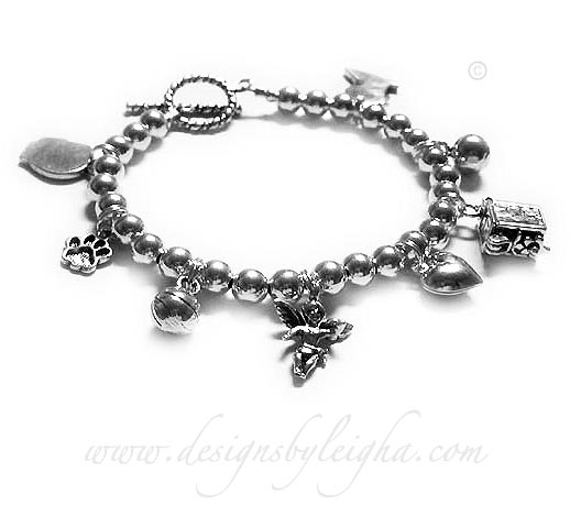 This Charm Bracelet is shown with 8 charms; boy profile, paw print, basketball, angel with wings, puffed heart, prayer box, soccer ball, girl profile with an upgraded heart toggle clasp.