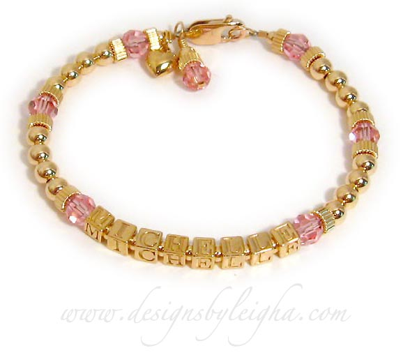 One-string Gold Block Mother Bracelet (DBL-GG2) with 1 name (Michelle) and October or Pink Birthstone 6mm Swarovski crystals. They picked the Gold Lobster Claw Clasp. They added a Gold Puffed Heart charm and a Pink Birthstone Crystal Dangle Charm.
