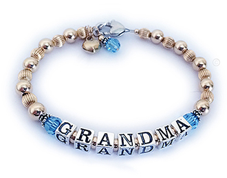 This is a Gold Grandma Bracelet. They put GRANDMA on the bracelet with Aquamarine or March Swarovski crystals before and after GRANDMA. They also added 3 things to their order: A Heart Lobster Claw Clasp, A 14k gold-plated Puffed Heart Charm and an Aquamarine or March Birthstone Crystal Dangle.