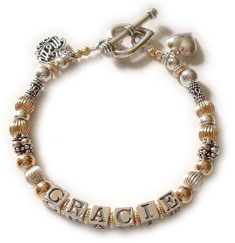 DBL-G6-1 string  This is a 1- bracelet with 1 name. Enter: GRACIE This is a 1-string Gold Mothers Name Bracelet with GRACIE. They added a Filigree MOM charm, a Puffed Heart charm and they upgraded from the free lobster claps to a Heavy Heart Toggle clasp.  ~ ~ ~