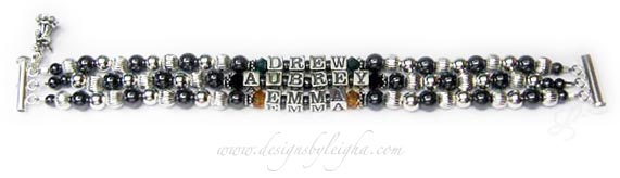 DBL-Hematite 2 - 3 string with 3 names  Enter: DREW/May, AUBREY/Feb, EMMA/Nov  This Hematite and Sterling Silver Mother Bracelet is shown on a 3-string slide clasp an 3 names: Drew with May or Emerald Swarovski crystals, Aubrey with February or Amethyst Swarovski crystals and Emma with November or Golden Topaz Swarovski crystals. They added the free Swarovski birthstone crystals before and after each childs' name and they added an Angel with a Harp charm. I recommend a slide clasp with 3 or more strings but you may pick which ever clasp is your favorite.