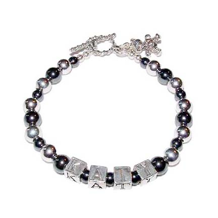 DBL-H1  This Hematite and Sterling Silver Name Bracelet is shown with 1 name - KATY. They added a Teddy Bear charm during the ordering process.
