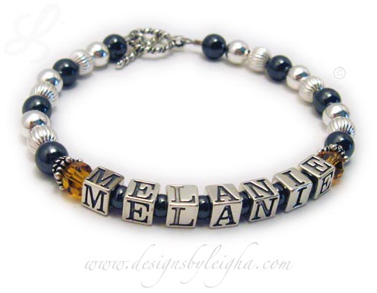 DBL-Hematite 2 - 1 string with 1 name  Enter: MELANIE/Nov  This Hematite and Sterling Silver Mother Bracelet is shown with a Twisted Toggle clasp with 1 name - Melanie. They added free November or Gold Topaz Swarovsk crystals before and after Melanie.