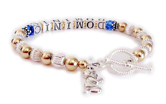 This Gold Mother Bracelet is shown with DOMINIC and Sapphire Swarovski birthstone crystals (free) before and after the name. They added a Praying Boy Charm. Shown with a Twisted Toggle clasp.