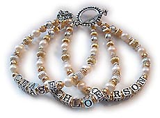 Mothers bracelet made with gold, silver and freshwater cultured pearls. A 3-string Mothers bracelet is shown, with 3 names. You may also have blank strings with this bracelet. Up to 9 letters per string. Additional letters are $1.50 each. THis bracelet is shown with a sterling silver LOVE charm. Charms are options. Go to the charms page to add charms to this bracelet before you check out.