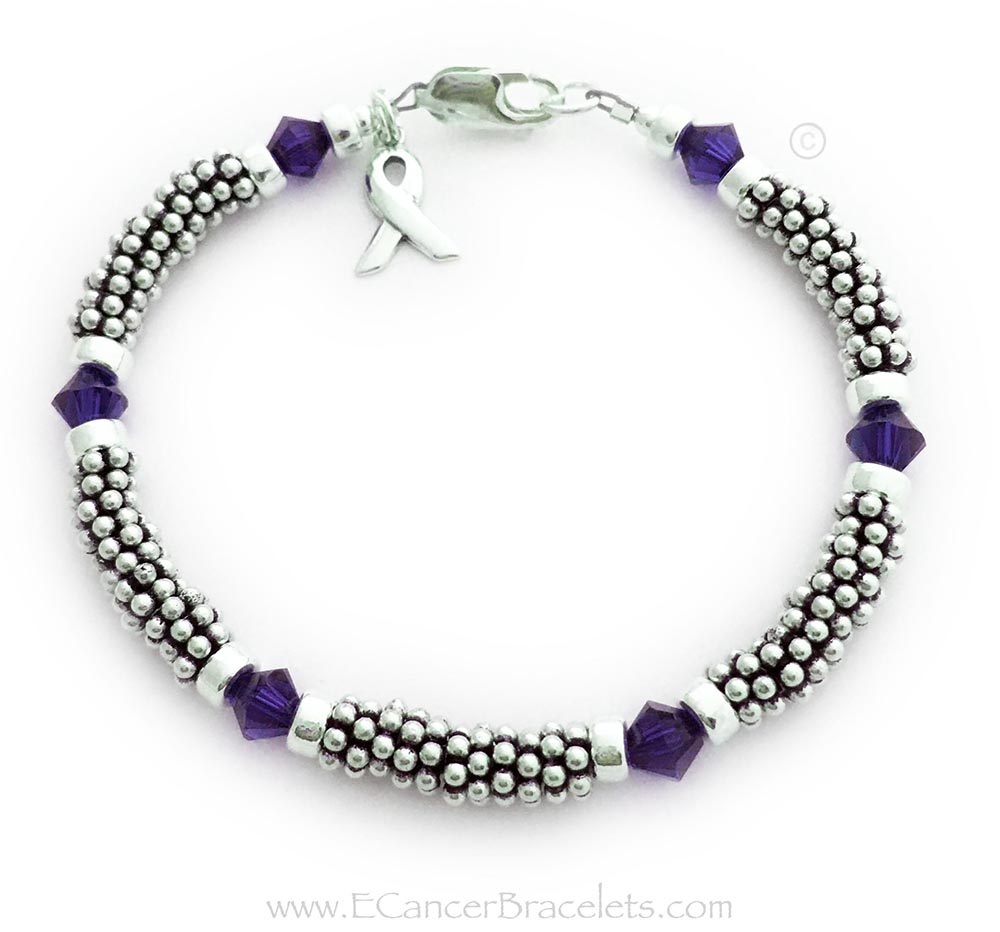 This is a 1-string Purple Ribbon 6mm Rope Bracelet with a Ribbon Charm and a Lobster Claw Clasp. The Sterling Silver Rope Chain Beads and Purple Swarovski Crystals are 6mm.