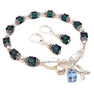 Donor Cancer Bracelets shown with an IN MEMORY bead, green crystals, a puffed heart charm, ribbon charm and an aquamarine crystal birthstone dangle. CBB-R28