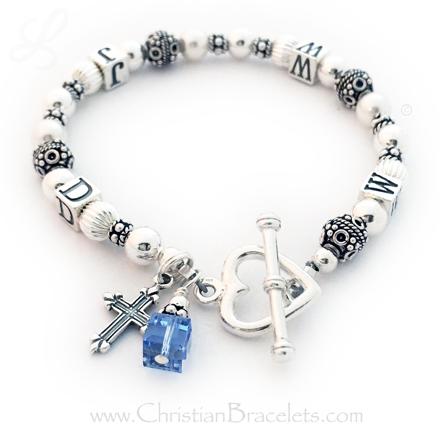 DBL-WWJD-1S  What Would Jesus Do Bracelet is shown with 3 add-ons: They added a Fancy Cross Charm, a December or Blue Topaz Birthstone Crystal Charm and upgraded to a Heart Toggle Clasp. Size: 7""